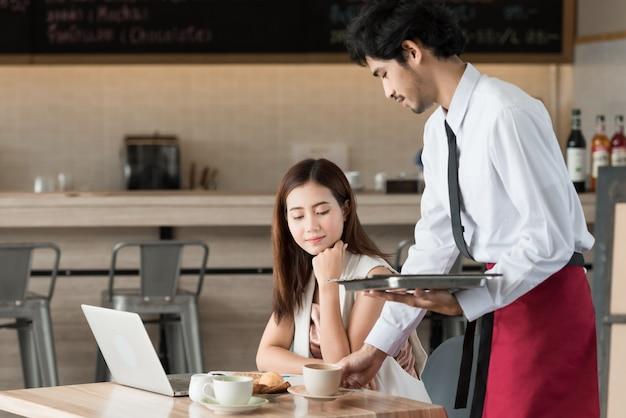 Ober serveren koffie aan klant die werken met laptop in café.