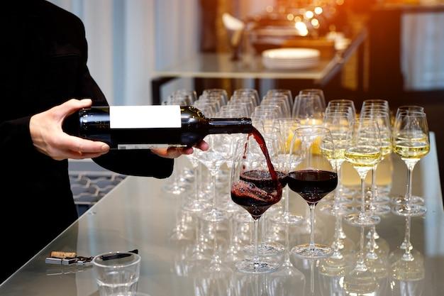 Ober vult een glas rode wijn door in een restaurant.