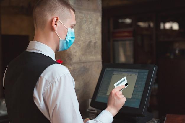 Ober werkt in een restaurant met een medisch masker.