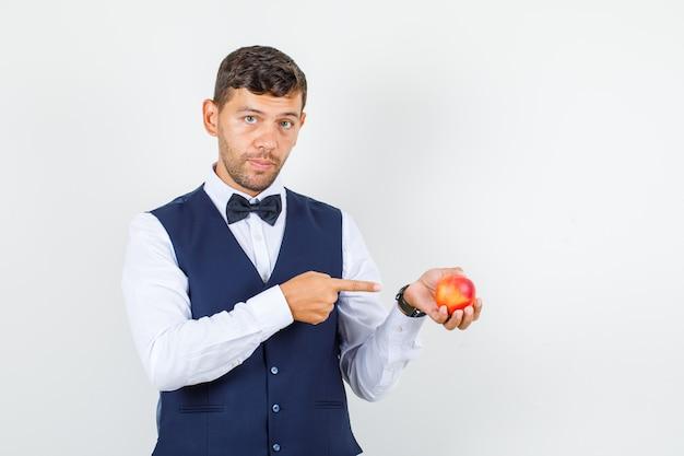 Ober wijzende vinger naar nectarine in overhemd, vest en op zoek naar serieuze, vooraanzicht.
