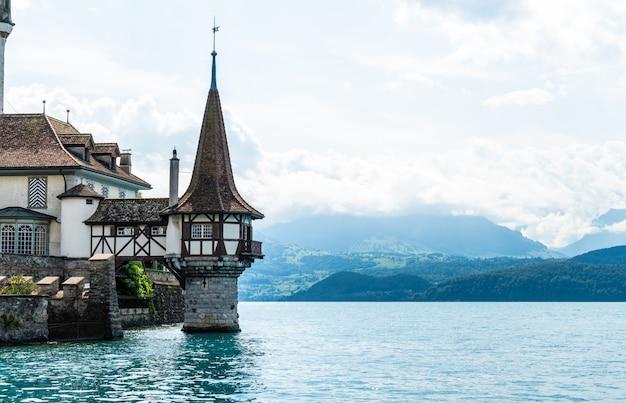 Oberhofen-kasteel met thun-meerachtergrond in zwitserland