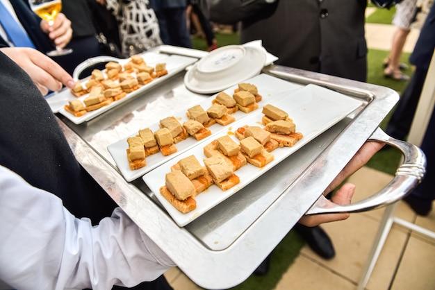 Obers die in dienbladen, snacks en tapas aan de gasten bij een bedrijfsdiner dienen.