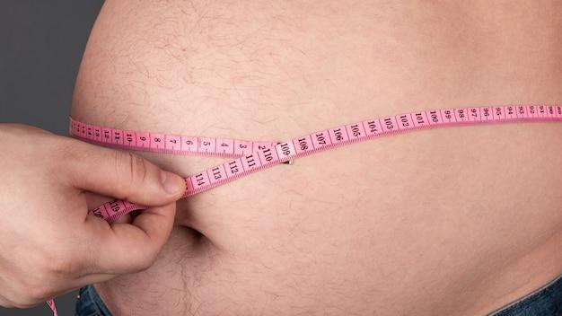 Obesitas concept, meet een grote dikke buik met een centimeter.