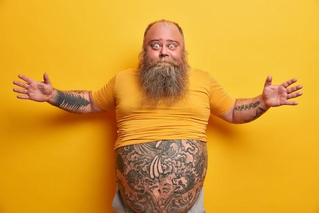 Obesitas en ongezonde levensstijl concept. verrast afgeluisterd oog man spreidt armen en vertelt over iets groots dat hij zag, gebaart actief, heeft getatoeëerd lichaam en grote buik, geïsoleerd op gele muur