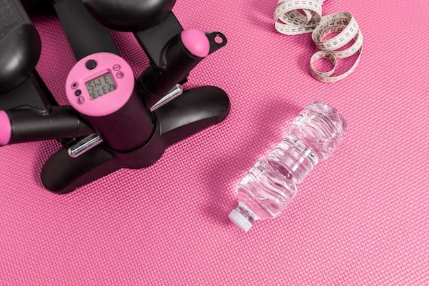 Objecten van het fitnessleven, stepper-machine om calorieën te verbranden, meetlint en waterfles op een roze achtergrondvloer.