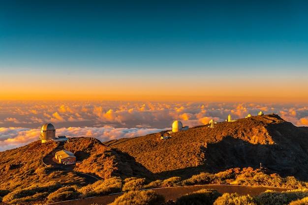 Observatoria van roque de los muchachos in de caldera de taburiente in een prachtige oranje zonsondergang, la palma, canarische eilanden. spanje