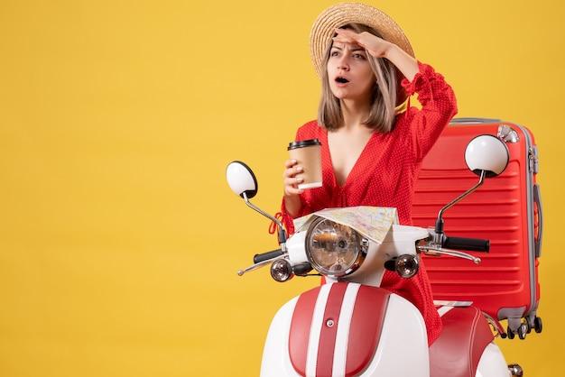 Observeren jonge dame in rode jurk met koffiekopje in de buurt van bromfiets