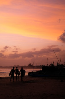 Oceaan kust bij zonsondergang silhouetten van boten en mensen surfers naar het strand gaan