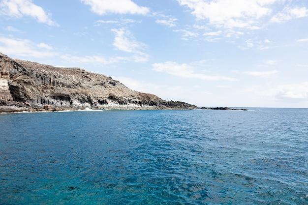 Oceaan kuststreek met klippen en bewolkte hemel