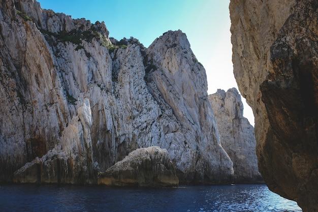 Oceaan omringd door de rotsachtige kliffen die glinsteren onder de blauwe lucht - geweldig voor achtergronden