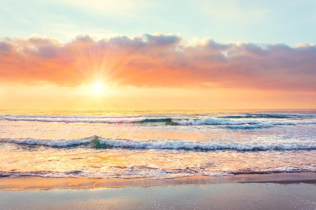 Oceaangolf op het strand in zonsondergangtijd, zonnestralen.