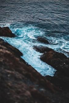 Oceaangolven die op rotsachtige kust overdag verpletteren