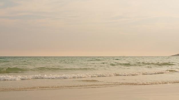 Oceaanstrandgolven op tropisch strand in zonsondergangtijd