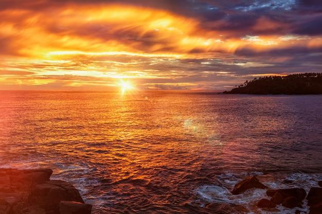 Oceaanzonsondergang met dramatische hemel