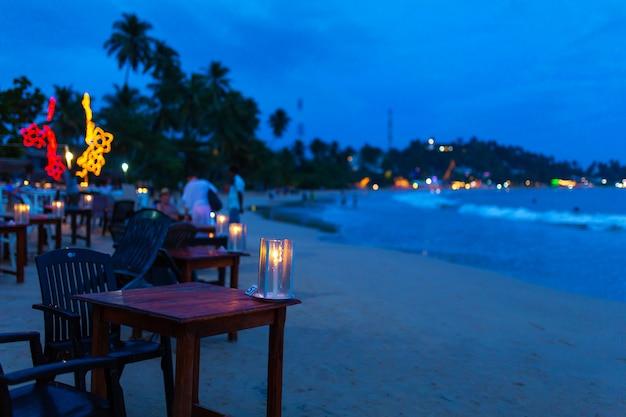Oceanfront restaurant met verlichting en tafels op een zandstrand