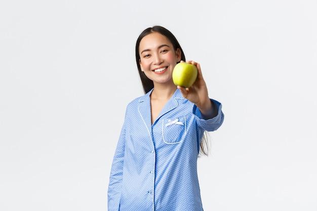 Ochtend, actieve en gezonde levensstijl en thuisconcept. glimlachend vriendelijk koreaans meisje in pyjama met groene appel en verrukt grijnzend, raad aan om fruit te eten om fit te blijven, witte achtergrond.