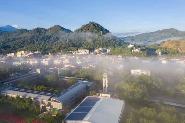 Ochtend bewolkt landschap met gebouwen onder wolken en mist in yuchi township, nantou, taiwan