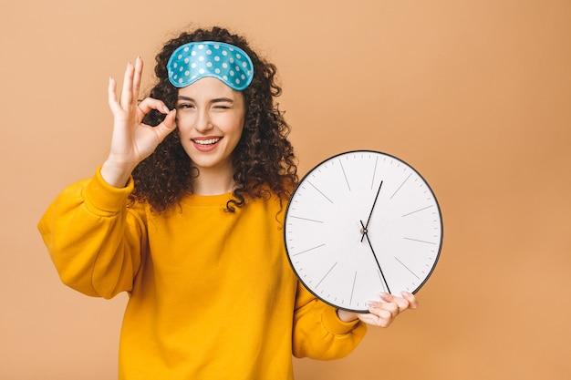 Ochtend concept. het mooie krullende jonge vrouw stellen over beige achtergrond met klok en slaapmasker. ok teken.