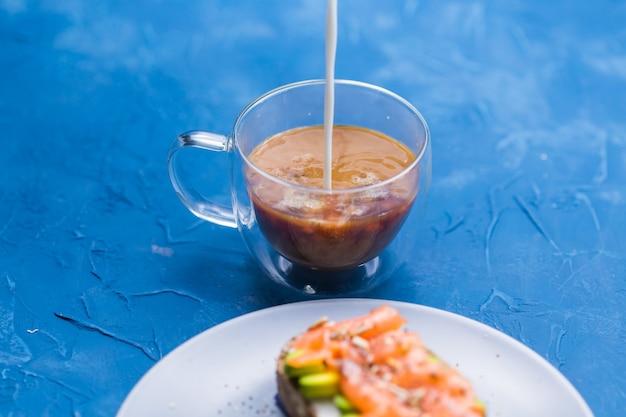 Ochtend- en ontbijtconcept - room in een kopje koffie gieten