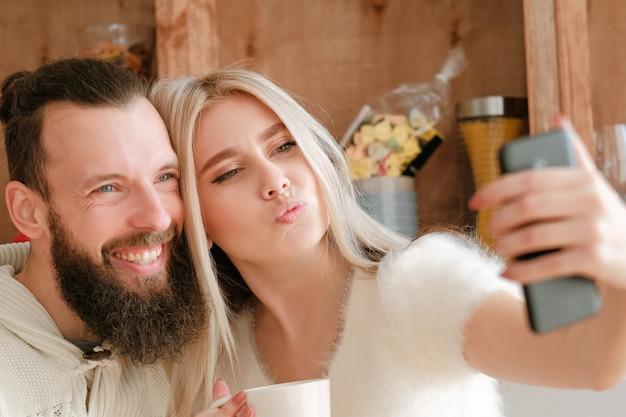 Ochtend familieplezier. closeup portret van paar koffie drinken in de keuken, met behulp van de camera van de smartphone om selfie te nemen.