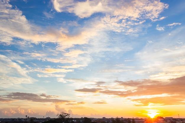 Ochtend hemelachtergrond met kleurrijke oranje zonsopgang en pluizige wolken