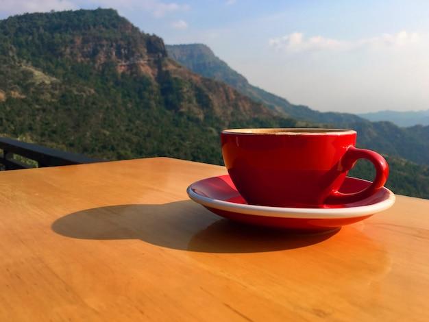 Ochtend hete latte kunstkoffie in een rode kop op houten balkon bij de helling
