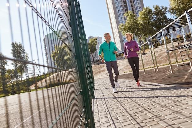Ochtend jog actief volwassen familiepaar in sportkleding die vroeg samen in het stadion loopt