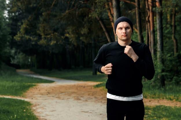 Ochtend jog in het park, een man in een zwart sportpak die rond de ruimte van het parkexemplaar loopt