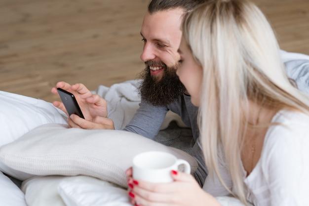 Ochtend jong koppel wordt ritueel wakker. bebaarde man en vrouw in bed met kopje drank en smartphone.