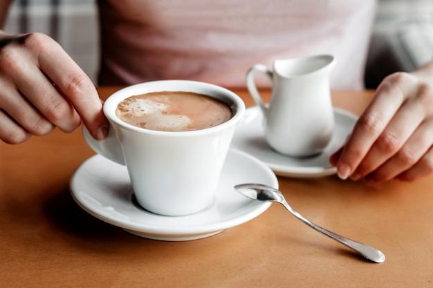 Ochtend koffie. close-up van de handen van vrouwen met koffiekop in een koffie. vrouwelijke handen met kopjes koffie op een houten tafel in een café, vintage kleurtoon
