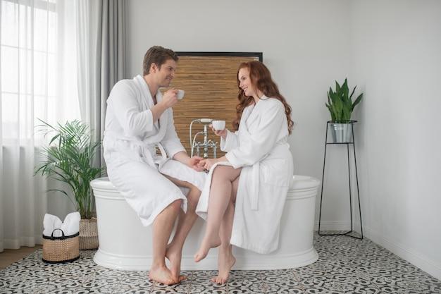 Ochtend koffie. een stel in witte badjassen dat koffie drinkt in een badkamer en zich verontwaardigd voelt