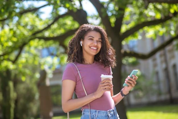 Ochtend koffie. glimlachende mulatta met een koffiekopje in handen in het park