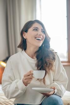 Ochtend koffie. mooie jonge vrouw zittend op het bed en koffie drinken