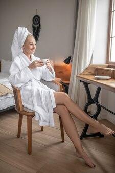 Ochtend koffie. mooie vrouw in een wit gewaad met koffie na het bad