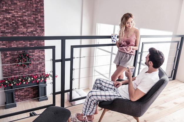 Ochtend koffie. slanke blonde langharige vrouw in een mooie lingerie in gesprek met haar man terwijl ze 's ochtends koffie drinkt