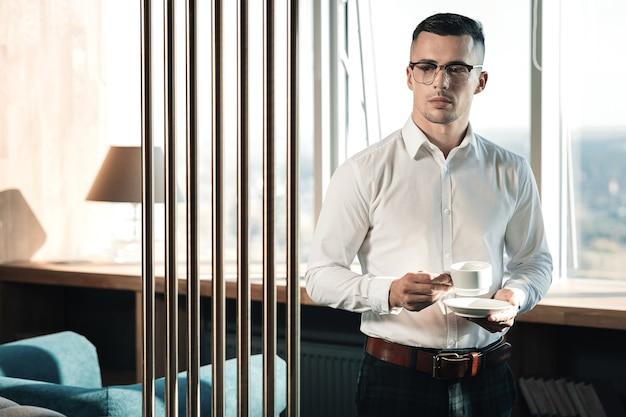 Ochtend koffie. stijlvolle jonge veelbelovende econoom die zich dichtbij venster bevindt die koffie in de ochtend drinkt