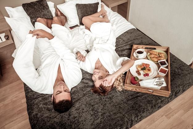 Ochtend met echtgenoot. blondharige vrouw voelt zich geweldig genieten van de ochtend met haar man in het hotel