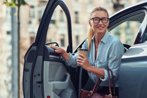Ochtend met koffie modieuze glimlachende zakenvrouw van middelbare leeftijd met papieren kopje koffie en