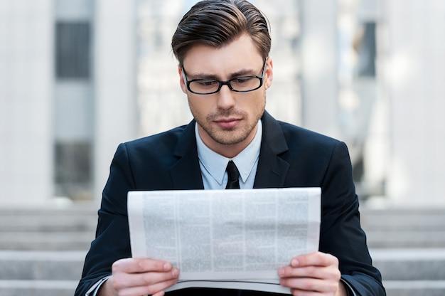 Ochtend nieuws. een jonge zakenman die buiten een krant leest