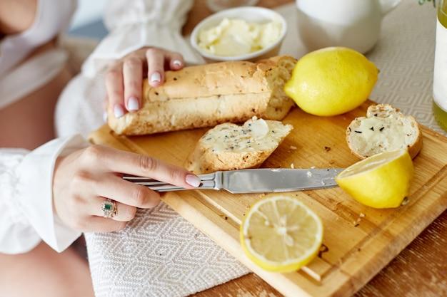 Ochtend ontbijt brood en boter, limonade en citroenen. een vrouw smeert boter op brood