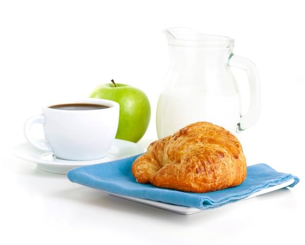 Ochtend ontbijt met koffie, melk, croissant en groene appel geïsoleerd op wit
