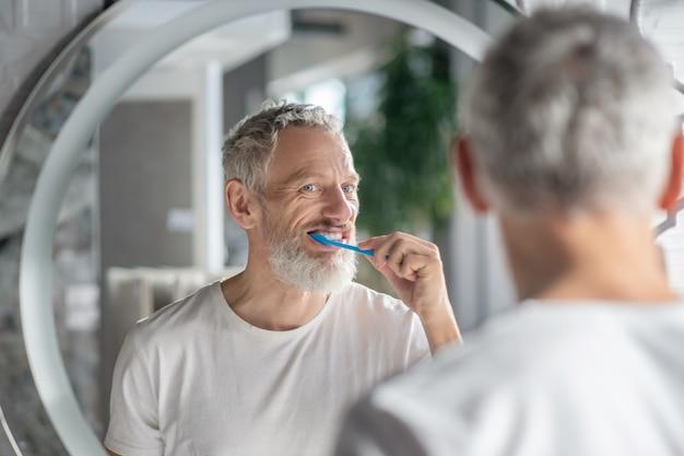 Ochtend routine. een grijsharige man die zijn tanden poetst bij de spiegel