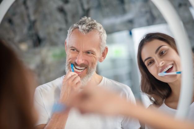 Ochtend routine. een man en een vrouw die genieten van samen hun tanden poetsen