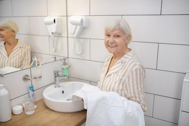 Ochtend routine. grijsharige vrouw in de badkamer met een handdoek in de hand