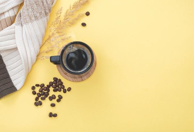 Ochtend samenstelling sjaal op tafel met koffiemok, koffiebonen. herfstseizoen