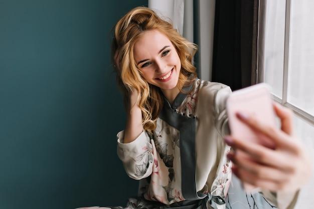 Ochtend selfie van jonge mooie vrouw, gelukkig, vrolijk meisje. ze draagt een zijden pyjama, heeft golvend blond haar en zit op de vensterbank in een kamer met een turquoise muur.