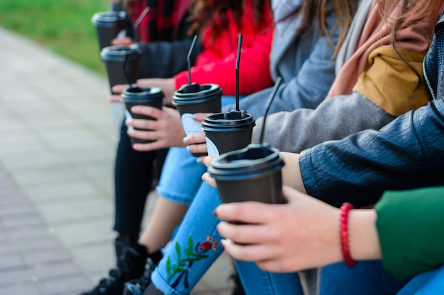 Ochtend straatkoffie, meisjes die koffie drinken in een lokaal park.