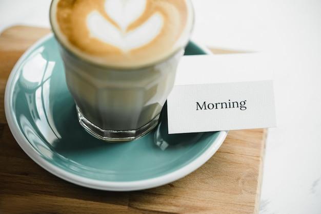Ochtend tekst tabelkaart met cappuccino koffie klaar om te drinken