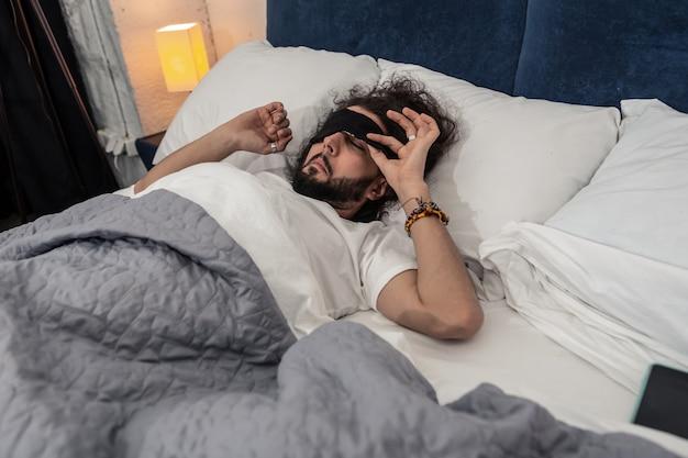 Ochtend tijd. aardige slaperige man die zijn oogmasker afdoet terwijl hij 's ochtends wakker wordt