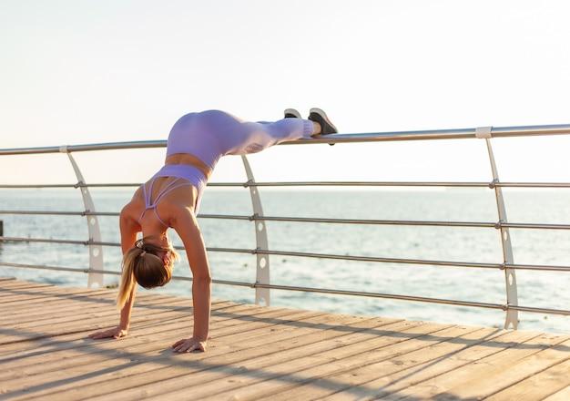 Ochtend training concept. jonge geschikte vrouw in sportkleding die opdrukoefeningoefening doen bij zonsopgang op strand
